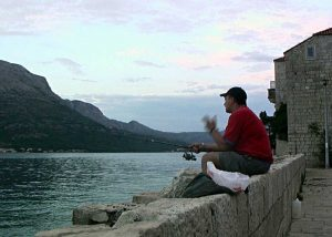 Fishing in Sveti Nikola, Korcula - Patient fisherman sitting at the wall and waiting for fish ..