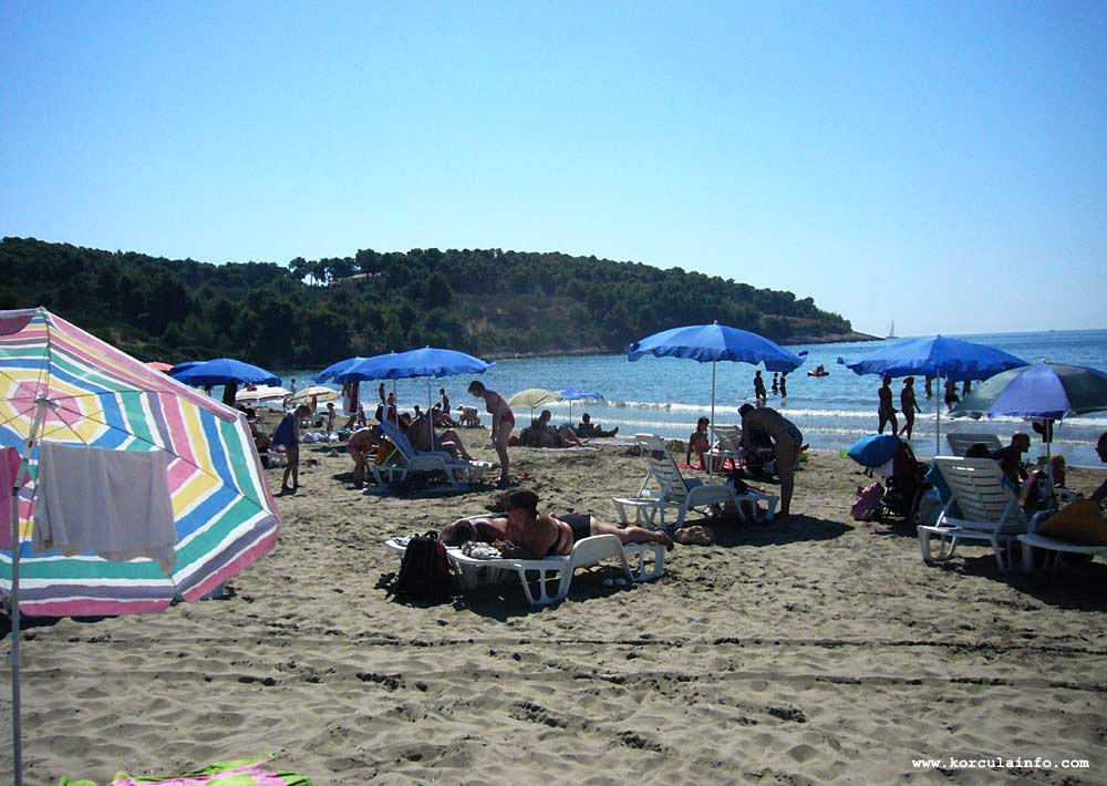 Parasols, sand and beach lounge chairs at Vela Przina