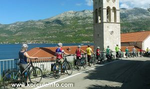 Group of cyclist pushing bikes in one way street, Sveti Nikola, Korcula